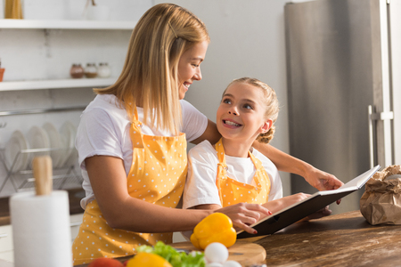 Beautiful happy mother and daughter smiling each other and reading cookbook in kitchen