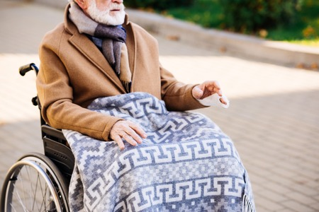 Cropped shot of senior disabled man in wheelchair with plaid on legs on street Stock Photo