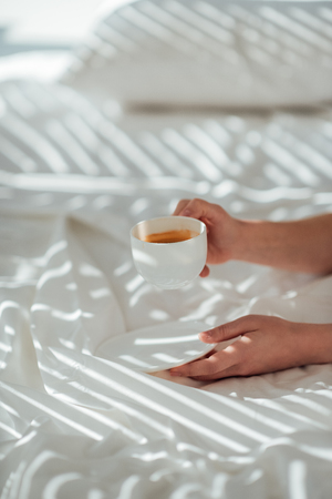Partial view of woman with cup of coffee in bed in morning Reklamní fotografie