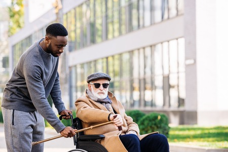 African american man giving walking stick to senior disabled man in wheelchair on street Banque d'images