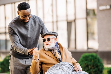 African american man giving joint to senior disabled man in wheelchair while they spending time together on street