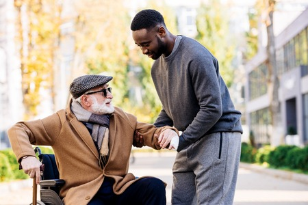 Young African american cuidador helping senior disabled man to get up from wheelchair on street Stock Photo