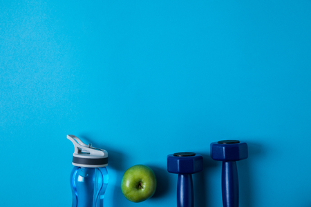 Elevated view of arranged sport bottle, green apple and dumbbells isolated on blue, minimalist concept