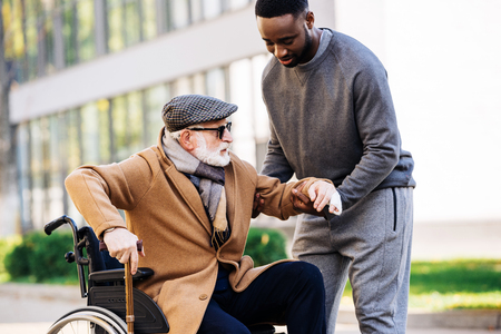 Young African american man helping senior disabled man to get up from wheelchair on street