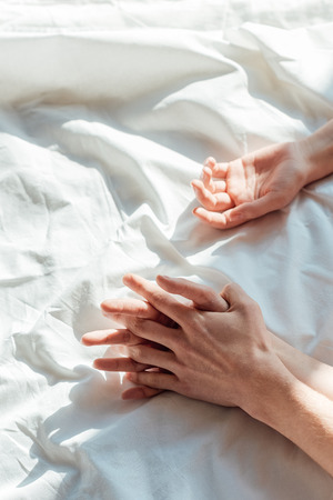 Partial view of couple in live holding hands while lying in bed together