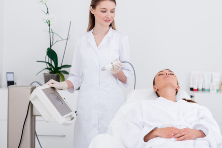 young woman lying on massage table in cosmetology salon with cosmetologist near by