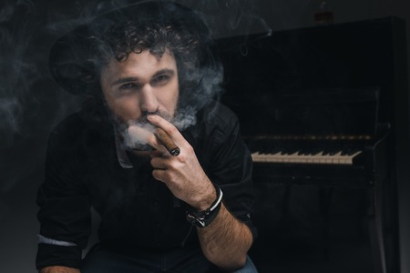 handsome musician smoking cigar in front of piano on black
