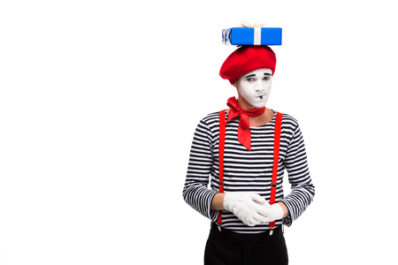 skeptical mime standing with gift box on head isolated on white