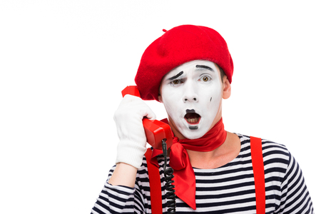 shocked mime talking by stationary telephone isolated on white