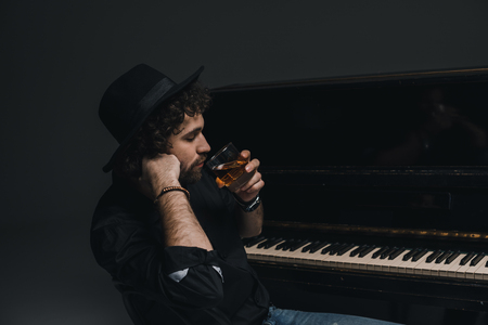 handsome musician drinking whiskey near piano on black 写真素材
