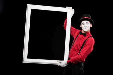 smiling mime holding frame isolated on black