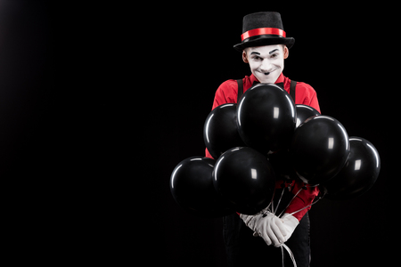 grimacing mime with bundle of helium balloons isolated on black Stock Photo