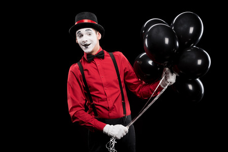 smiling mime holding bundle of black balloons isolated on black
