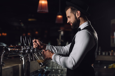 side view of bartender pouring beer from beer taps into glass