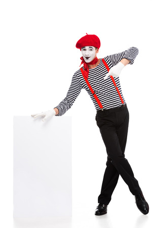 cheerful mime pointing on empty board isolated on white