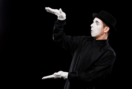 surprised mime showing size of something isolated on black