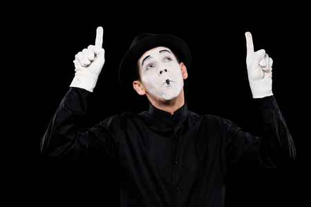 grimacing mime pointing on something isolated on black Фото со стока - 111217132