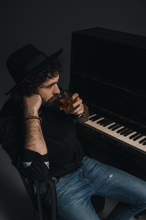 man with glass of whiskey sitting near piano on black