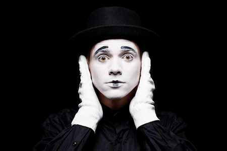 mime covering ears and looking at camera isolated on black Stock Photo