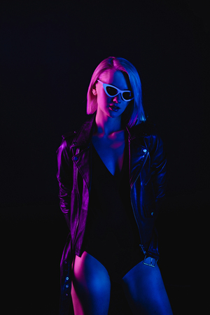 fashionable girl posing in black leather jacket and sunglasses, isolated on black 免版税图像