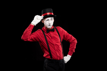 mime winking and greeting with hat isolated on black Stock Photo
