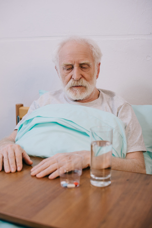 Old man looking sadly at pills on table Фото со стока