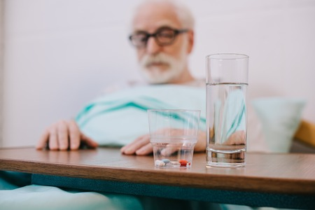 Pills and glass of water in front of senior man in hospital ward Фото со стока