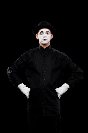 mime standing with hands akimbo and looking at camera isolated on black