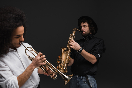 duet of musicians playing trumpet and saxophone on black