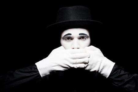 mime covering mouth and looking at camera isolated on black