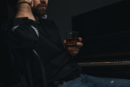 cropped shot of man with glass of whiskey sitting near piano on black