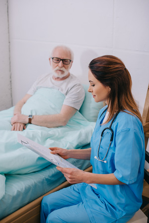Nurse explaining medical advice to old patient in bed Stock Photo