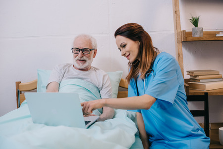 Nurse pointing at laptop in senior patient hands Stock Photo