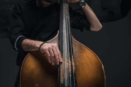 cropped shot of man playing contrabass on black Banque d'images - 111217313