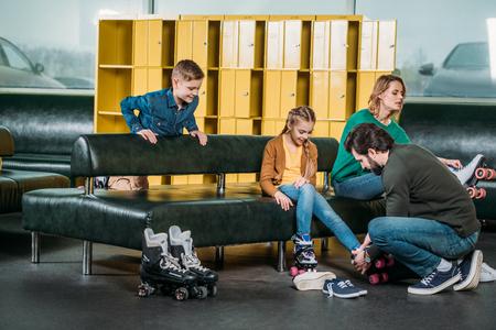 family wearing roller skates before skating in skate park