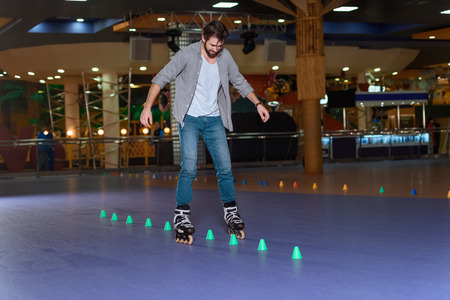 man in roller skates skating on roller rink with cones