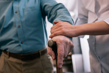 Close-up view of cane in hand of senior man supported by doctor Stock Photo - 111217392