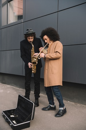 duet of stylish street musicians playing trumpet and saxophone outdoors