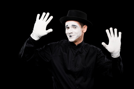 smiling mime performing and touching something isolated on black Фото со стока