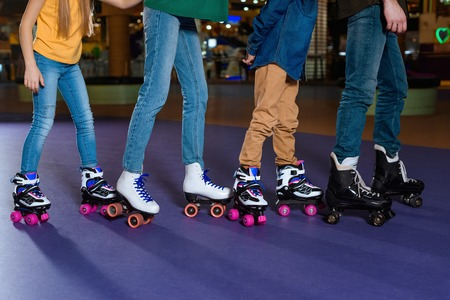 partial view of parents and kids skating on roller rink together Banco de Imagens