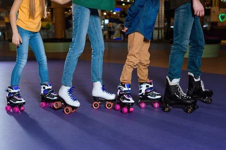 vue partielle des parents et des enfants patinant ensemble sur une patinoire Banque d'images