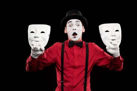 shocked mime holding two masks isolated on black Stock Photo