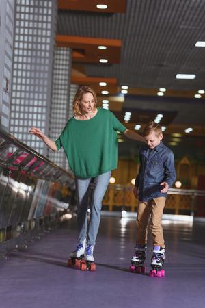 mother and little son skating together on roller rink