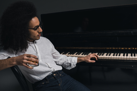 handsome young musician drinking whiskey and playing piano on black