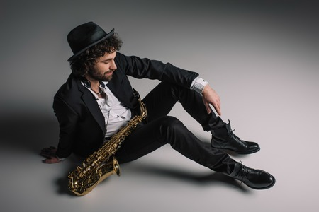 stylish musician sitting on floor with saxophone