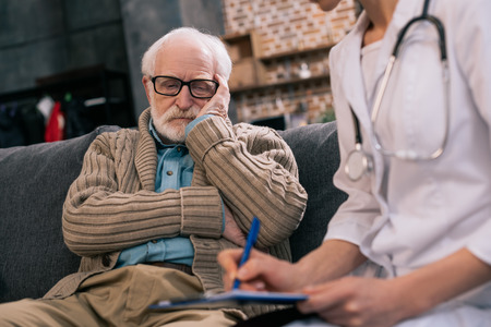 Sad senior man looking at doctor writing down medical complaints Stockfoto