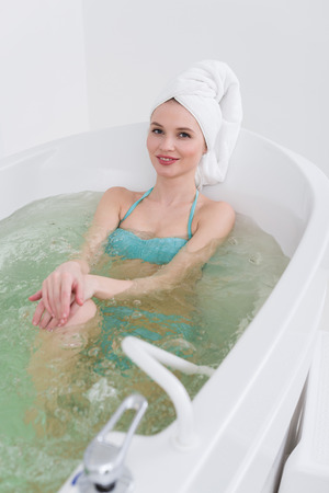smiling woman in swimming suit with towel on head relaxing in bath in spa salon