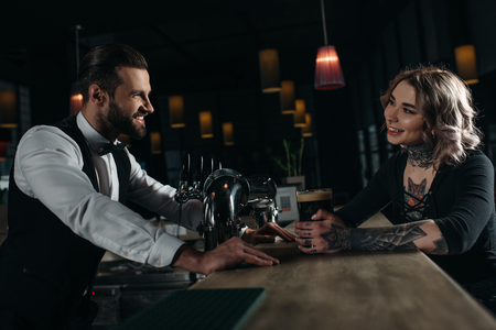 side view of smiling male bartender and girl looking at each other at bar counter Stok Fotoğraf - 111217502