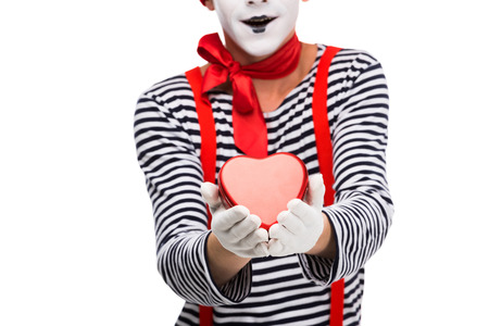 cropped image of mime holding heart shaped gift box isolated on white, st valentines day concept