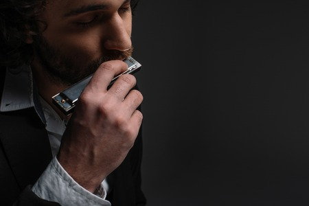 close-up portrait of handsome musician playing harmonica on black